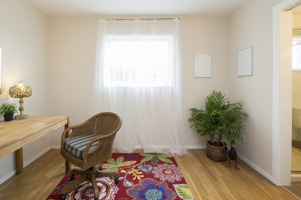 White walls, wooden furniture, and a quirky printed rug - all that you need for a marathon book reading session.